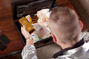 Ein Dieb der seine Beute in einen Koffer verstaut mit Euo-Scheinen und Gold